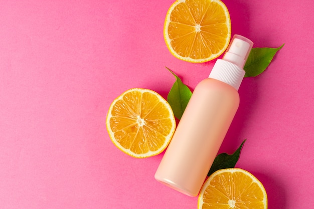 Cosmetic bottle with sliced citrus fruits on bright pink
