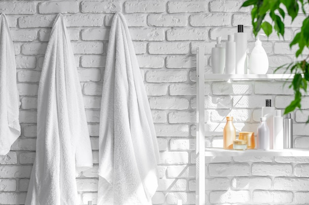 Cosmetic bottles against white bathroom wall background