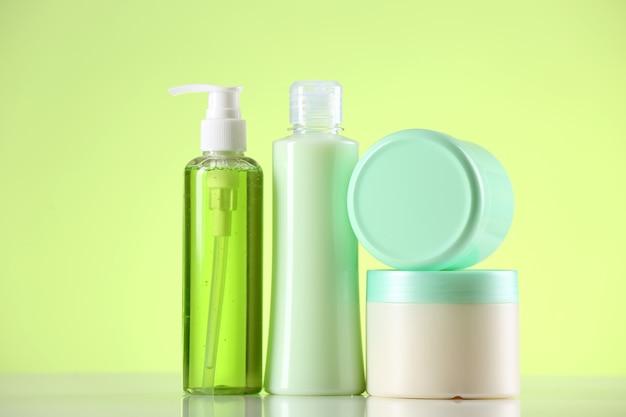Cosmetic bottles on light green