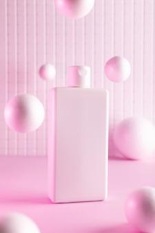 Косметические бутылки с летающими шарами в розовом неоновом свете, макет