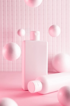 Cosmetic bottles with flying balls in a pink neon light, mock up