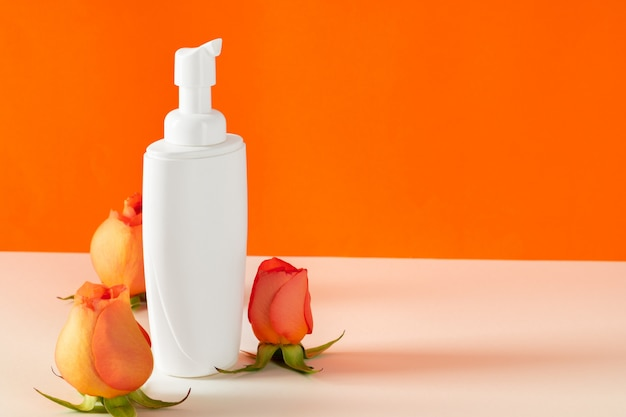 Cosmetic bottles with rose petals, copy space