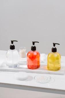 Косметические флаконы с гелем для душа, лосьоном для тела или шампунем и банные полотенца. ванные принадлежности.