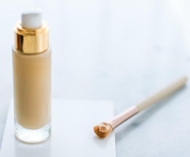 Косметический брендинг гламур и концепция ухода за кожей бутылка тонального крема и кисть для контуринга на мар ...