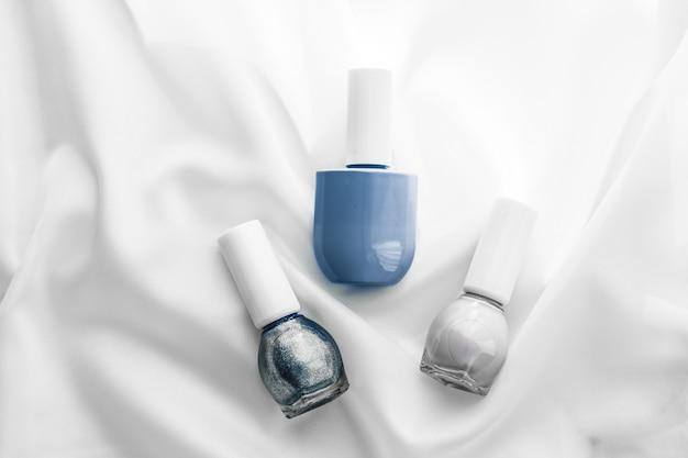 化粧品ブランディングサロンとグラマーコンセプトシルク背景のマニキュアボトルフレンチマニキュア製品と高級美容ブランドと休日のフラットレイアートデザインのためのネイルポリッシュ化粧品