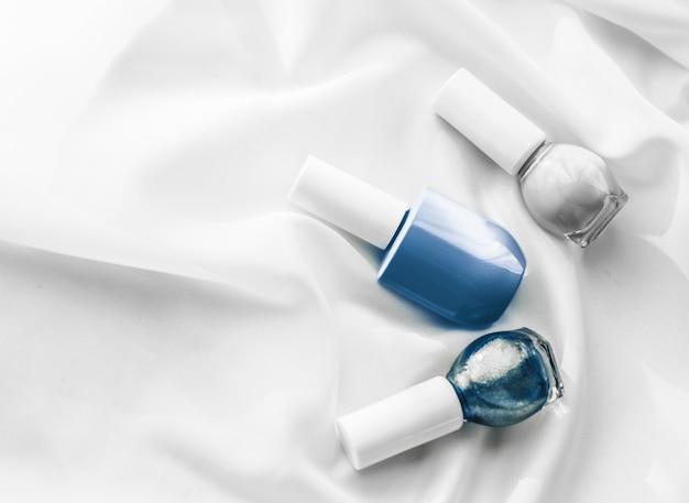 シルクの背景にフランスのマニキュア製品とマニキュア化粧品の高級美容ブランドとホリデー フラットレイ アート デザインの化粧品ブランド サロンと魅力的なコンセプトのマニキュア ボトル