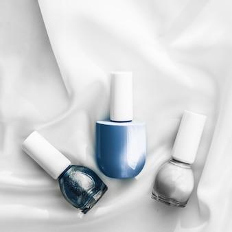 Косметический брендинг салон и гламурная концепция бутылки лака для ногтей на шелковом фоне продукты для французского маникюра и лак для ногтей косметика для косметики класса люкс и праздничный плоский арт-дизайн