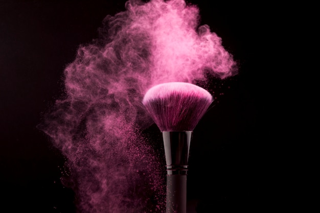 Cosmetic brush in cloud of pink powder on dark background