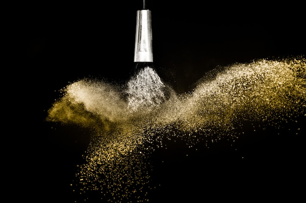 Cosmetic brush with golden cosmetic powder spreading