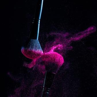 Косметические кисти и взрыв красочных порошков. красочный взрыв под косметикой.