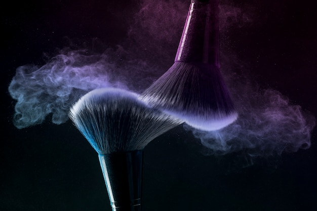 Cosmetic brushes in cloud of makeup powder on dark background