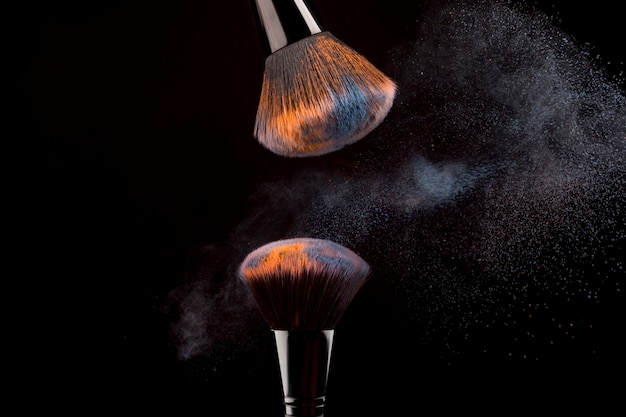 Cosmetic brushes with mist of powder on dark background