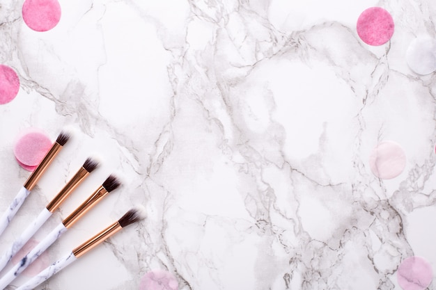 Cosmetic brushes with pink decorations on marble