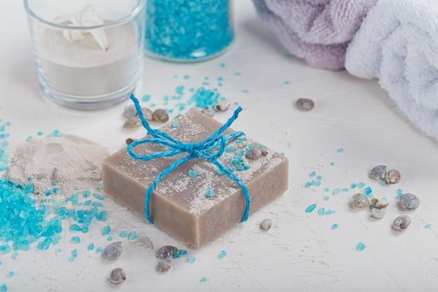 化粧品の粘土粉、自家製粘土石鹸、白い背景の上の青いバス海塩。フェイスケア、ボディケア、スパのコンセプト。