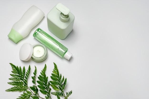 Cosmetic containers with green herbal leaves, blank label package for branding. moisturizing cream, shampoo, tonic, face and body skin care.