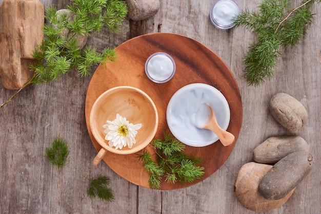 Косметический крем и свежие листья на фоне деревянного стола