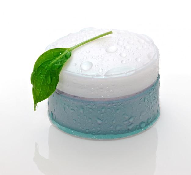白で隔離される化粧品のクリームと緑の葉