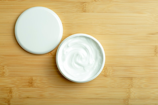 Cosmetic cream background white cosmetic cream for skin and body in an open white jar on a wooden ba...