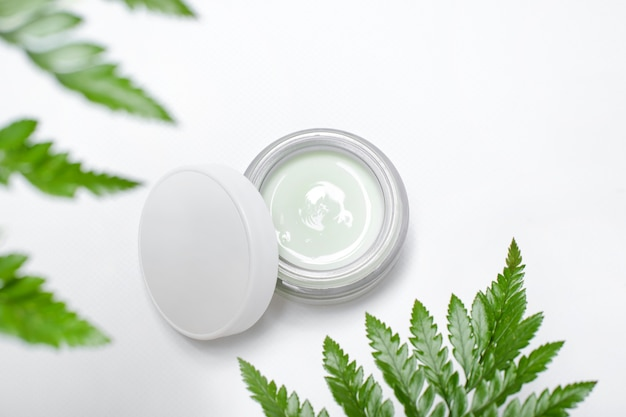 Cosmetic cream in container and fresh green leaves on white. homemade spa, jar of organic cream, natural cosmetics, beauty products.