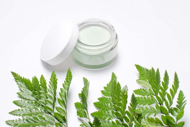 Cosmetic cream in container and fresh green leaves on white. homemade spa, jar of organic cream, natural cosmetics, beauty products