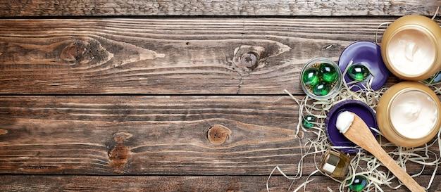 瓶の中の化粧品クリーム、ガラスの緑色のボール、木製の背景のガラス瓶の中の化粧品ローション。