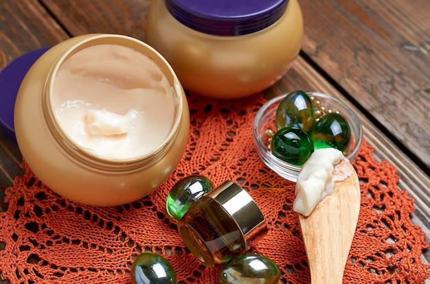 瓶の中の化粧品クリーム、ガラスの緑色のボール、木製のテーブルの上のガラスの瓶の中の化粧品ローション
