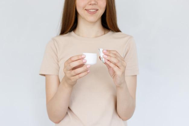 女性のクローズアップの手に化粧用クリーム