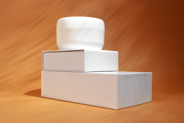Cosmetic cream jar on brown wall.  body or face care product container.