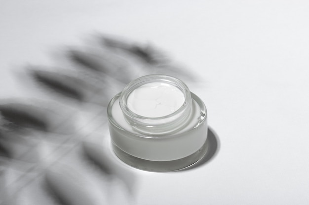 Cosmetic cream or mask in a glass jar with hard shadows from the leaves on a white background. natural organic care for face and body skin. view from above.