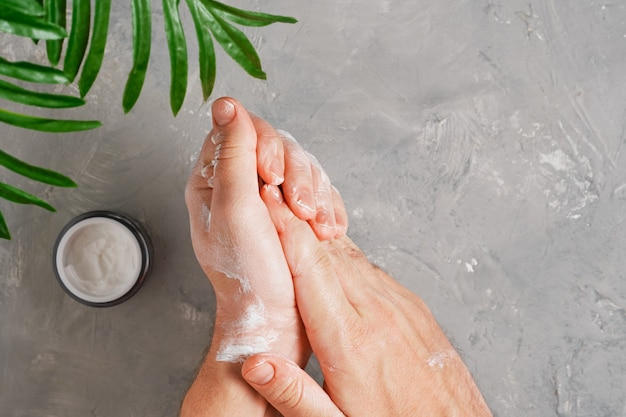 Косметический крем на мужских руках, баночки с кремом и зелеными листьями на нейтральном сером столе. плоская планировка, вид сверху. мужчина наносит органический увлажняющий крем для рук. концепция ухода за кожей рук