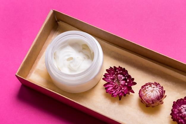 ピンクのテーブルの上の化粧品クリーム