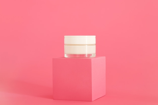 Упаковка косметического крема, стоящая на розовом подиуме. презентация крема на розовом фоне. макет.