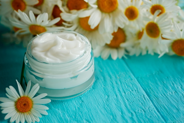 Cosmetic cream with camomile flower or a body and face on blue wooden table