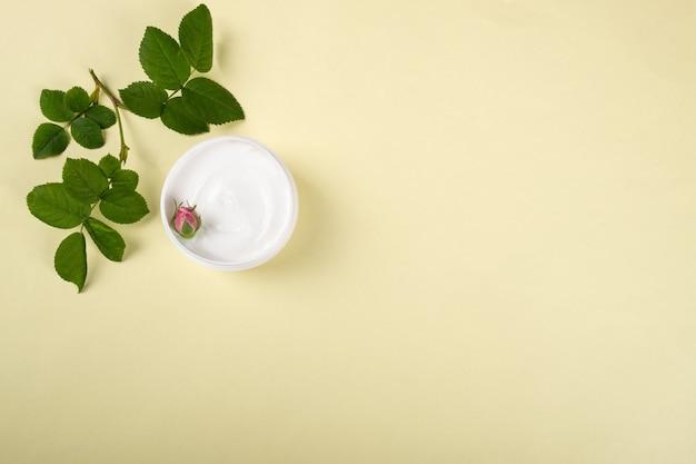 노란색 배경에 복사 공간이 있는 장미 향미용 스킨 케어 플랫이 있는 코스메틱 크림