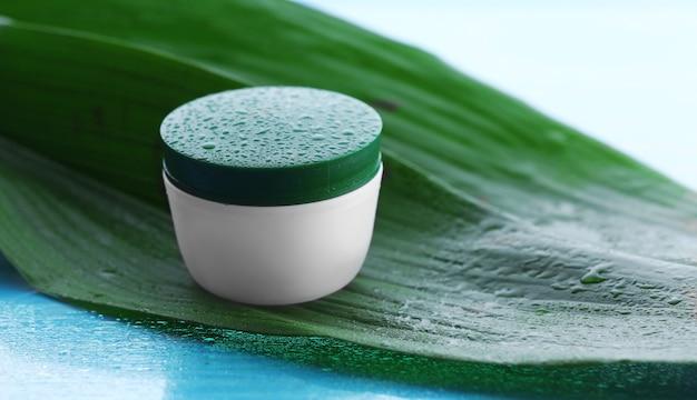 빛에 녹색 잎에 물 방울과 화장품 크림