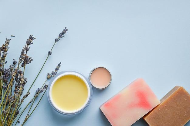Cosmetic creams, lip balm, blue background