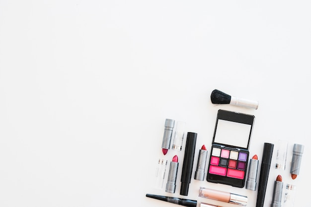 Cosmetic eye shadows; different shades of lipstick; and brush arranged on white background