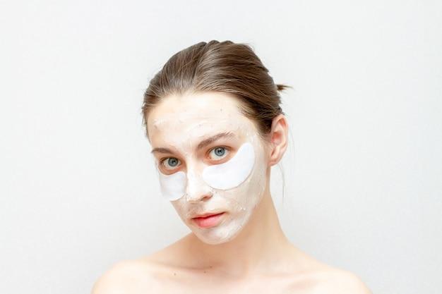 아름 다운 소녀에 화장품 얼굴 마스크입니다. 젊은 여자는 눈 패치를 사용합니다.