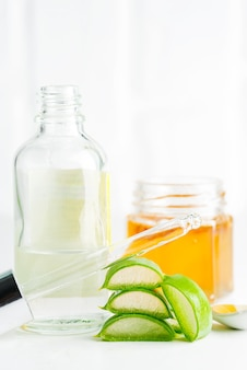 Cosmetic homemade lotion or essential oil from natural sliced aloe vera plant in glass bottles against light grey background.