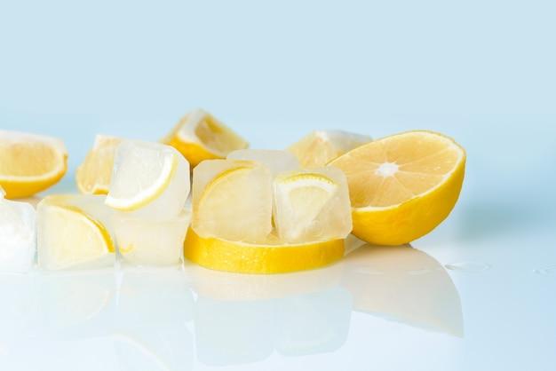 Cosmetic ice cubes with lemon and vitamin c for skin care on a blue light background, natural organic ingredients for home care, detox. place for text.
