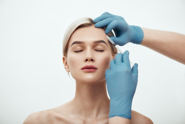 Cosmetic injection portrait of young pretty woman keeping eyes closed while doctors hand in blue