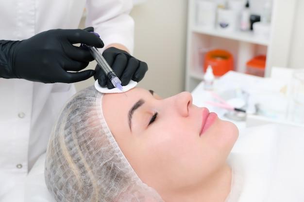 피부 회춘을 위한 화장품 주사. 미용사는 젊은 여성의 피부에 주사기를 주입합니다.