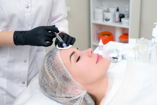 肌の若返りのための美容注射。美容師は若い女性の皮膚に注射器を注射します。