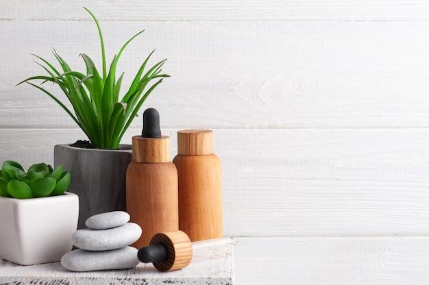 木製の背景にクリーム、保湿ボディローション、エッセンシャルオイルを入れた化粧品の瓶。環境にやさしいパッケージの天然オーガニックスパ