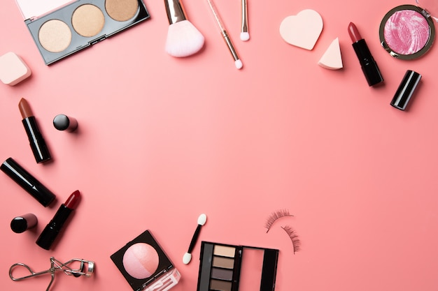 Cosmetic make up flat lay pink background copy space text beauty