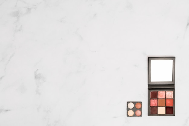 白いテクスチャ背景の隅に化粧品アイシャドウとフェイスパウダーパレット