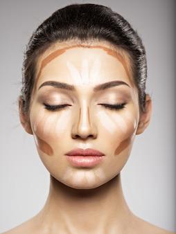 화장품 메이크업 색조 파운데이션은 여성의 얼굴에 있습니다. 미용 치료 개념. 소녀는 메이크업을합니다.