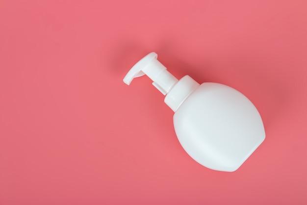 パステルピンクの背景にボトルを化粧品のモックアップ