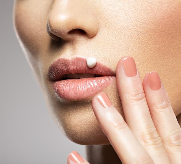 女性の唇に化粧品の保湿クリーム。スキンケアのコンセプト。美容トリートメントのコンセプト。