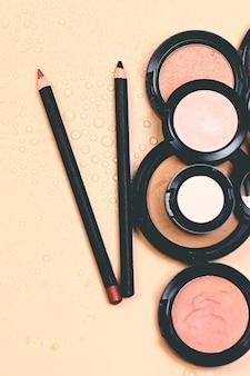 Косметическая естественная пастельная концепция. косметические средства для макияжа на пастельно-бежевом фоне. база для нейтрального макияжа. очень мягкий выборочный фокус